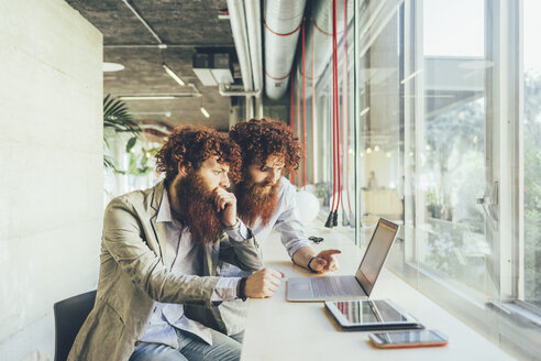 Male adult hipster twins pointing at laptop in office - CUF16020