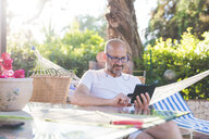 Man sitting outdoors at table using smartphone - CUF16056