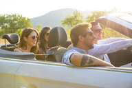 Four adult friends driving on rural road in convertible, Majorca, Spain - CUF16098