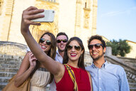 Two tourist couples in sunglasses taking selfie in front of church, Calvia, Majorca, Spain - CUF16104