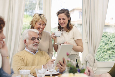 Senior Italian couple and daughter browsing digital tablet at breakfast table - CUF16200