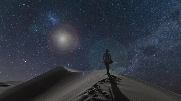 Silhouetted view of woman on dunes under starry night sky, Namib Desert, Namibia - CUF16290