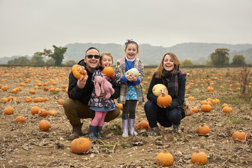 Portrait of parents and two daughters crouching in pumpkin field - CUF16335
