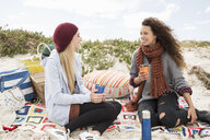 Two young women chatting beach picnic, Western Cape, South Africa - CUF16341