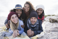 Portrait of young adult friends lying on top of each other on beach, Western Cape, South Africa - CUF16350