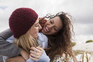 Two young female friends hugging at beach, Western Cape, South Africa - CUF16353