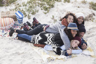 Young adult friends lying on top of each other having fun at beach, Western Cape, South Africa - CUF16359