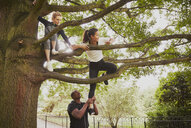 Personal trainer giving woman helping hand to climb park tree - CUF16368