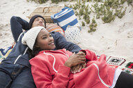 Young couple reclining on picnic blanket at beach, Western Cape, South Africa - CUF16371