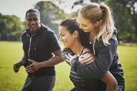 Personal trainer encouraging two women piggy backing in park - CUF16389