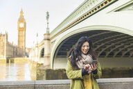 Young woman in front of Westminster bridge and Big Ben looking down using smartphone smiling, Thames river, London, UK - CUF16494