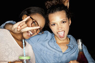 Young woman arm around friend looking at camera open mouthed doing rock sign - CUF16512