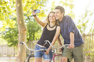 Young couple with bicycle taking selfie in park - CUF16569