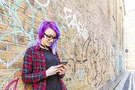 Woman using smartphone against graffiti wall - CUF16587
