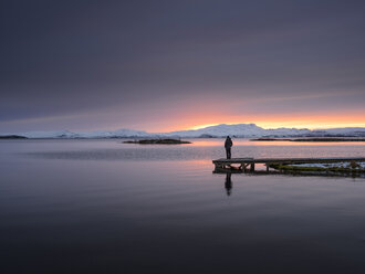 Man standing on pier by lake looking at sunset, Thingvellir, Iceland - CUF16599