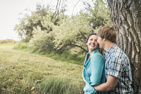 Romantic young couple leaning against tree - CUF16623