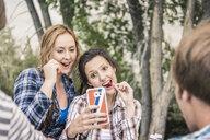 Over shoulder view of young women eating cherries taking smartphone selfie - CUF16647