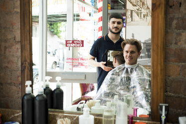 Mirror image of barber using mirror to show smiling customer haircut - CUF16740