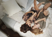 High angle view of two stylish beautiful young women lying on bed - CUF16836