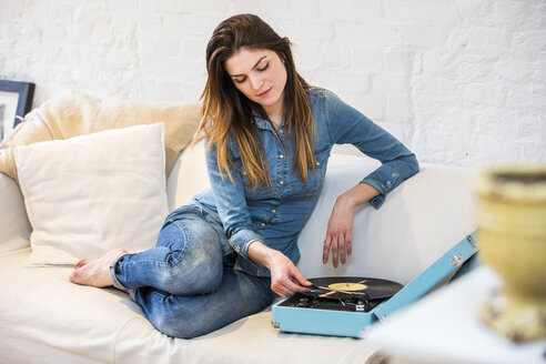 Young woman sitting on sofa listening to vintage record player - CUF16857