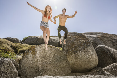 Couple outdoors, holding hands, jumping off of rock onto sand - CUF16941