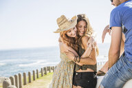 Mid adult friends hugging at coast, Cape Town, South Africa - CUF16950