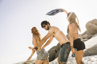 Three adult friends fooling around together on beach, Cape Town, South Africa - CUF16971