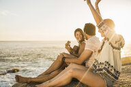 Three mid adults sitting on rocks playing acoustic guitar at sunset, Cape Town, South Africa - CUF17004