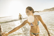 Mid adult woman wearing bikini playing with friends on beach, Cape Town, South Africa - CUF17037