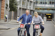 Mature dating couple laughing whilst cycling on hire bicycles, London, UK - CUF17079