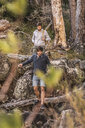 Male hikers hiking down forest rock formation, Deer Park, Cape Town, South Africa - CUF17097