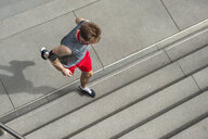 Young man exercising outdoors, running up steps, elevated view - CUF17121