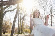 Woman wearing chiffon dress swinging on tree swing smiling - CUF17136