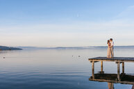 Full length side view of couple of wooden pier in ocean kissing - CUF17139