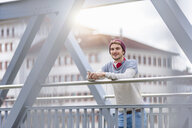 Man on bridge leaning against railings holding smartphone looking at camera smiling - CUF17145