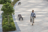 High angle view of young man walking in city carrying digital tablet, Dubai, United Arab Emirates - CUF17214