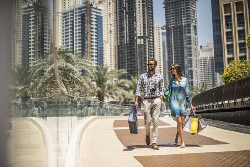 Tourist couple strolling on walkway carrying shopping bags, Dubai, United Arab Emirates - CUF17220