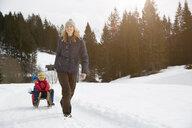 Woman pulling sons on toboggan in snow covered landscape, Elmau, Bavaria, Germany - CUF17259