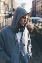 Man wearing hooded top and headphones, hands in pockets looking away - CUF17292