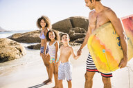 Bodyboarding couple and children on beach, Cape Town, South Africa - CUF17340