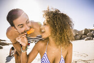 Couple sharing ice lolly on beach, Cape Town, South Africa - CUF17346