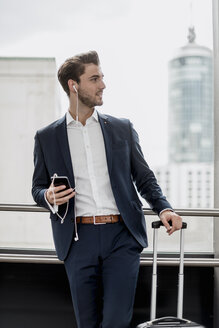 Young businessman at the window with cell phone, earbuds and rolling suitcase - DIGF04503