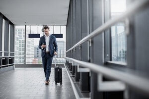 Young businessman in a passageway with cell phone, earbuds and rolling suitcase on the go - DIGF04506
