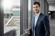 Portrait of smiling young businessman in a passageway with cell phone and earbuds - DIGF04509