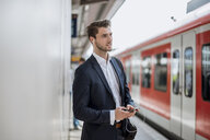Businessman at the station with earbuds and cell phone - DIGF04521