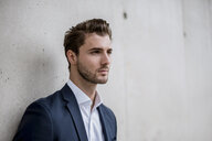 Portrait of businessman at concrete wall - DIGF04524