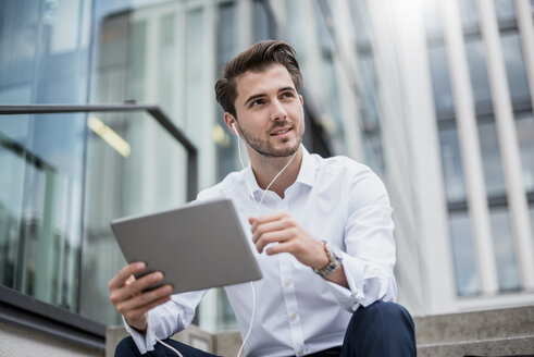 Smiling businessman sitting on stairs with earbuds and tablet - DIGF04530