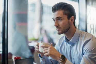 Young businessman drinking coffee in a cafe - DIGF04542