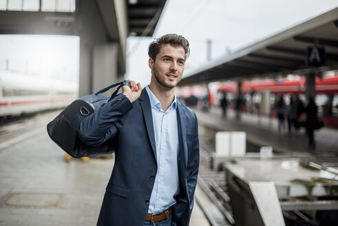 Smiling businessman with bag at the platform - DIGF04548
