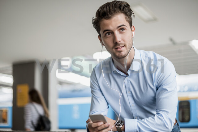 Businessman with cell phone and earbuds at the station - DIGF04554